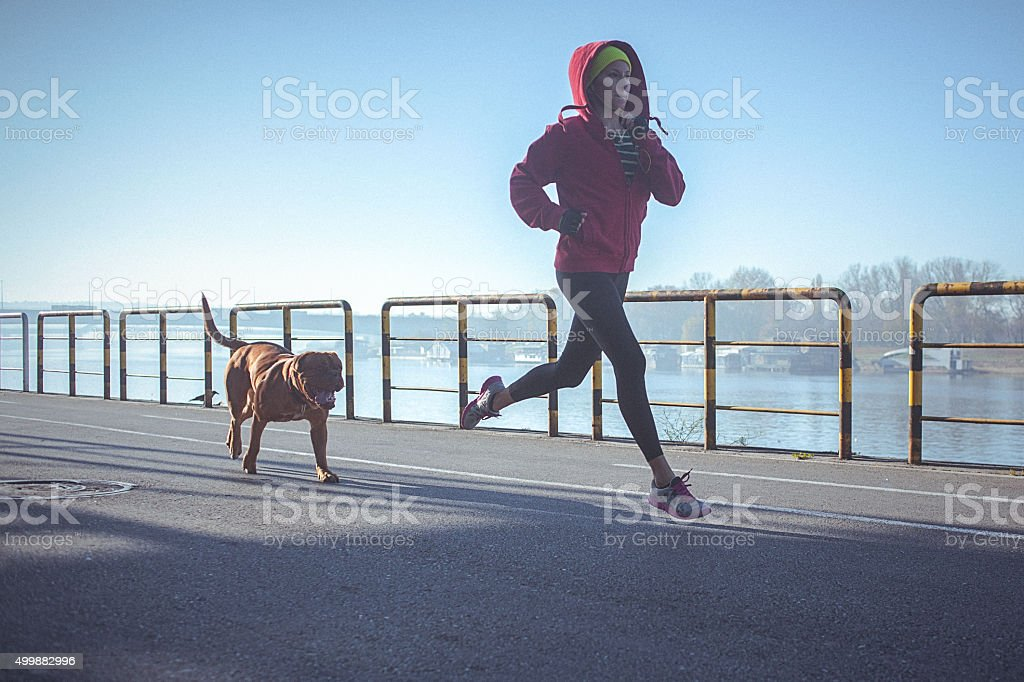 Young fit woman running with her dog on the riverbank stock photo