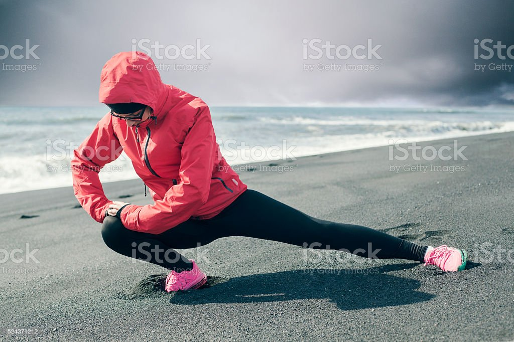 Young fit  woman stretches her leg after work out stock photo