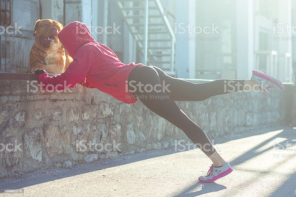 Young fit woman stretching after running stock photo