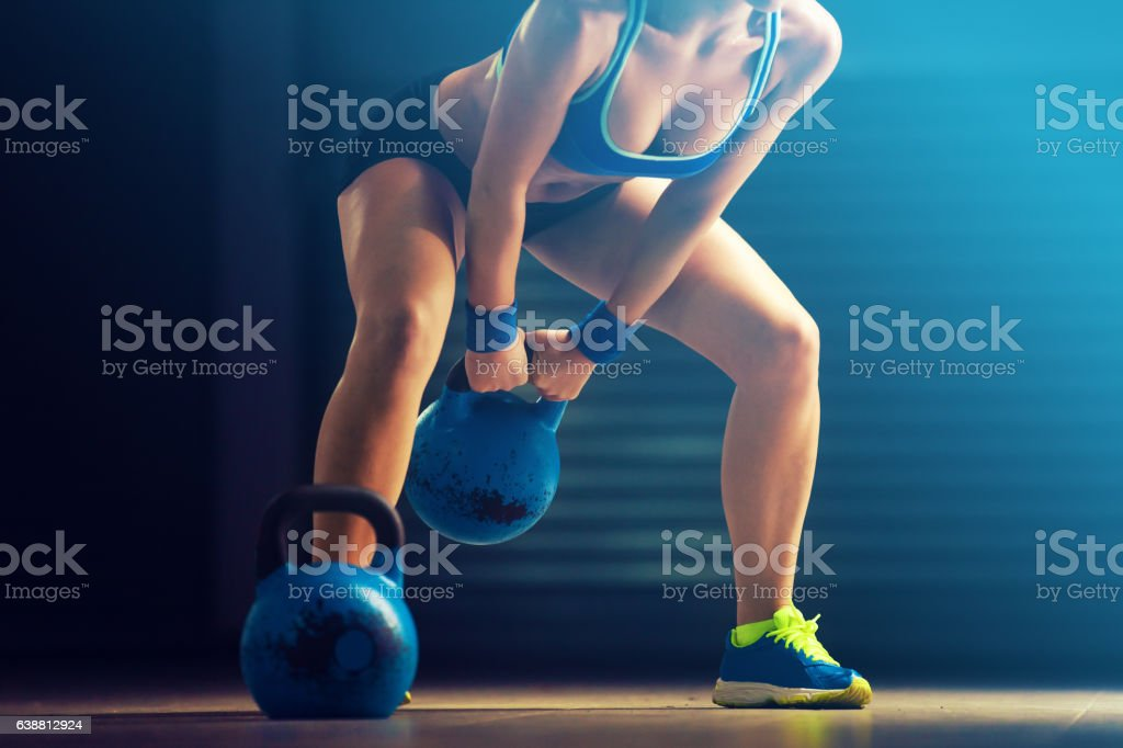 Young fit woman training by kettlebell. stock photo