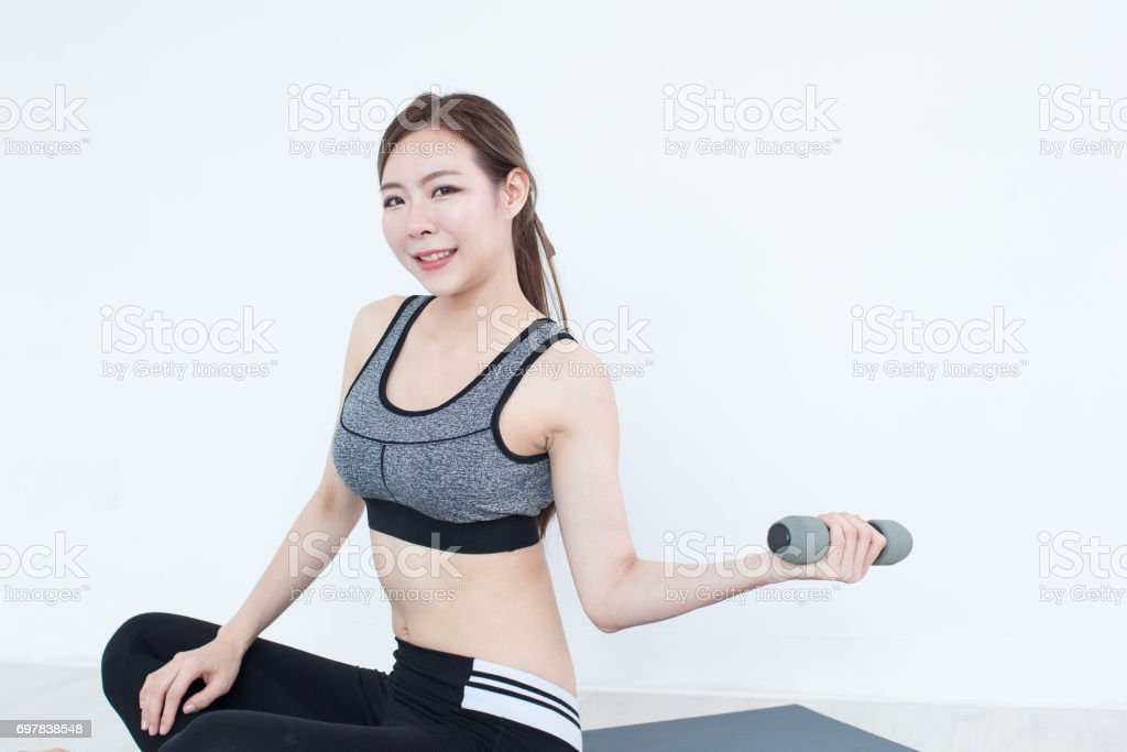 Young Fitness Asian girl lifting dumbbell, workout in bedroom, fitness, training and lifestyle concept stock photo