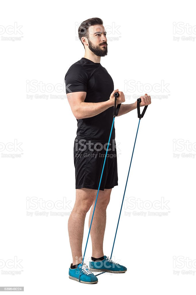 Young fitness athlete doing bicep curl exercise with resistance bands stock photo