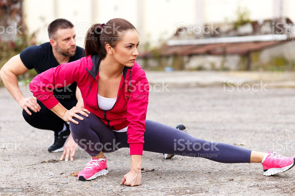 Young fitness couple stretching their muscles. stock photo