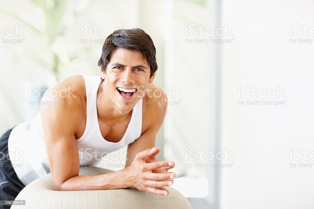 Young fitness male exercising on a ball royalty-free stock photo