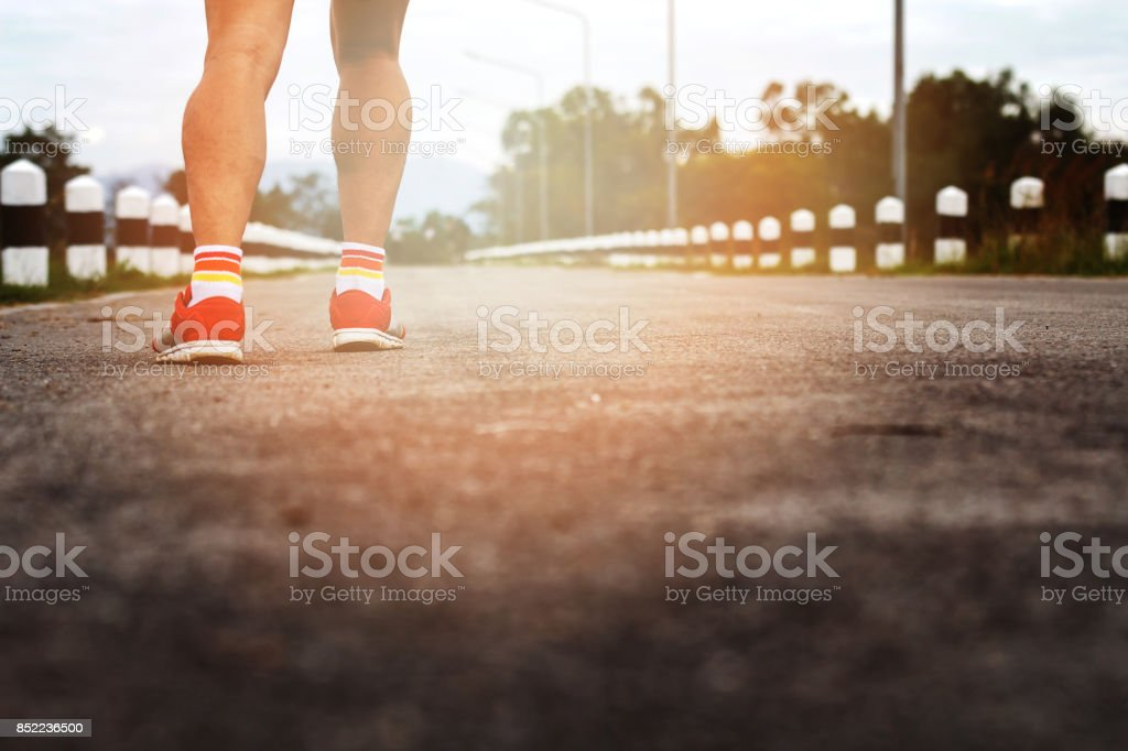 Young fitness man runner legs running on road stock photo