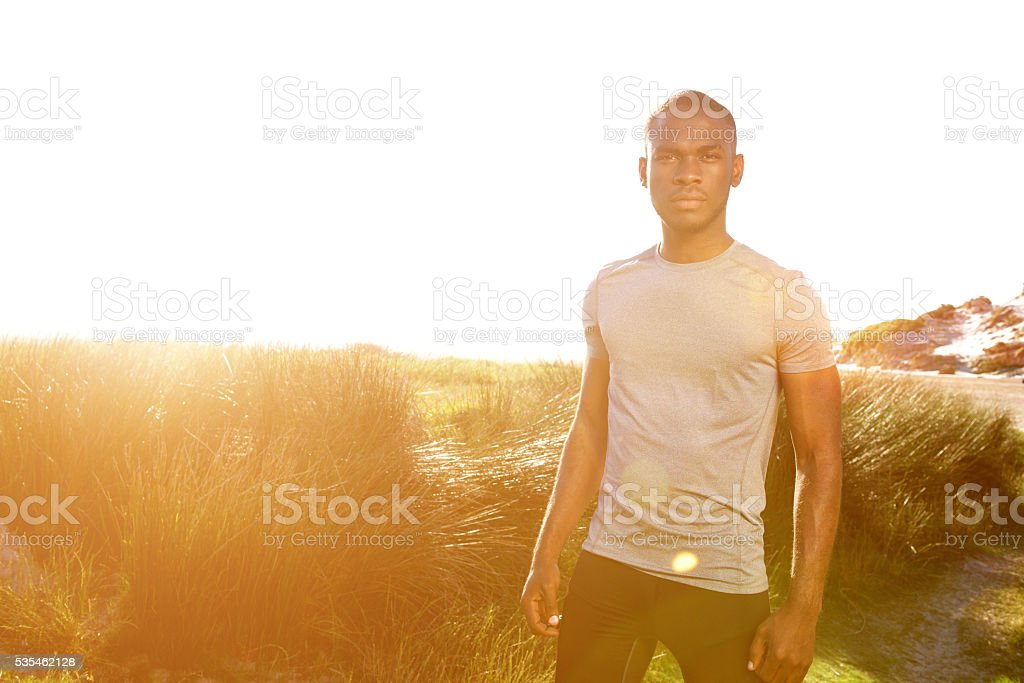 Young fitness man standing at the beach with bright sunlight stock photo