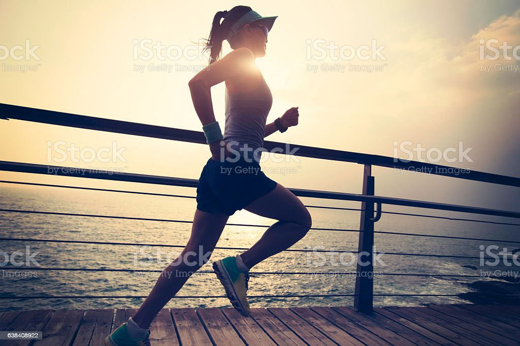 young fitness sports woman  trail runner running on seaside stock photo