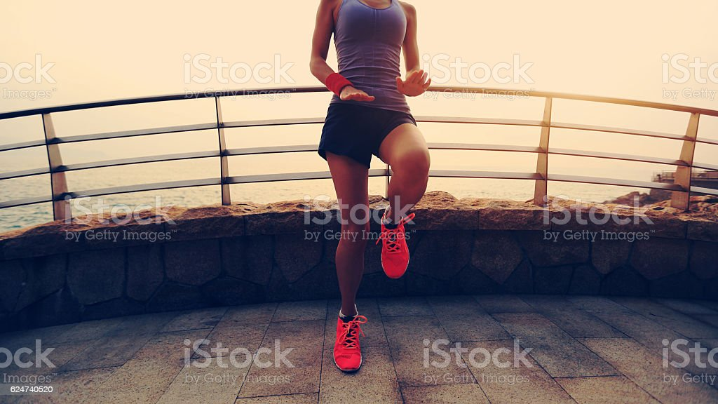 young fitness sports woman warm up on sunrise seaside stock photo
