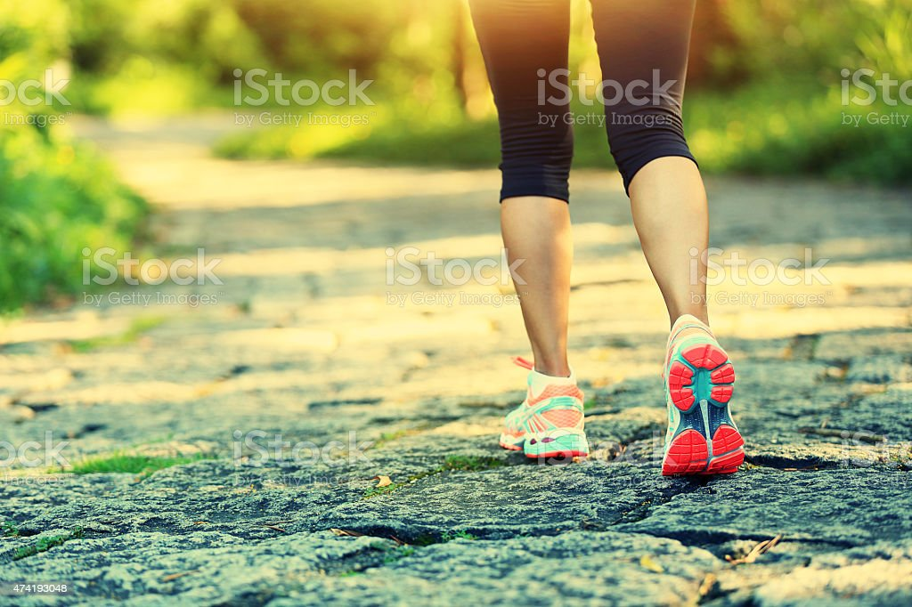 young fitness woman hiker legs at forest trail stock photo