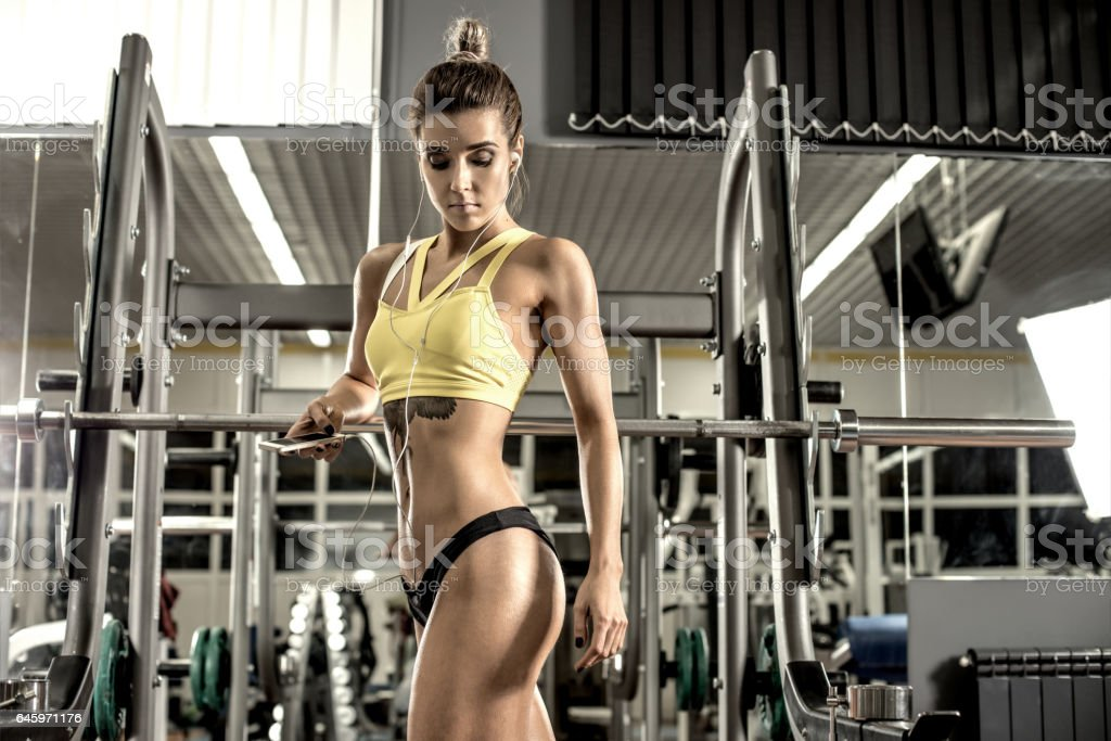 young fitness woman  in gym and listen music with headset stock photo
