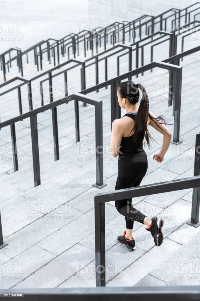 Young fitness woman in sportswear running down on stadium stairs stock photo
