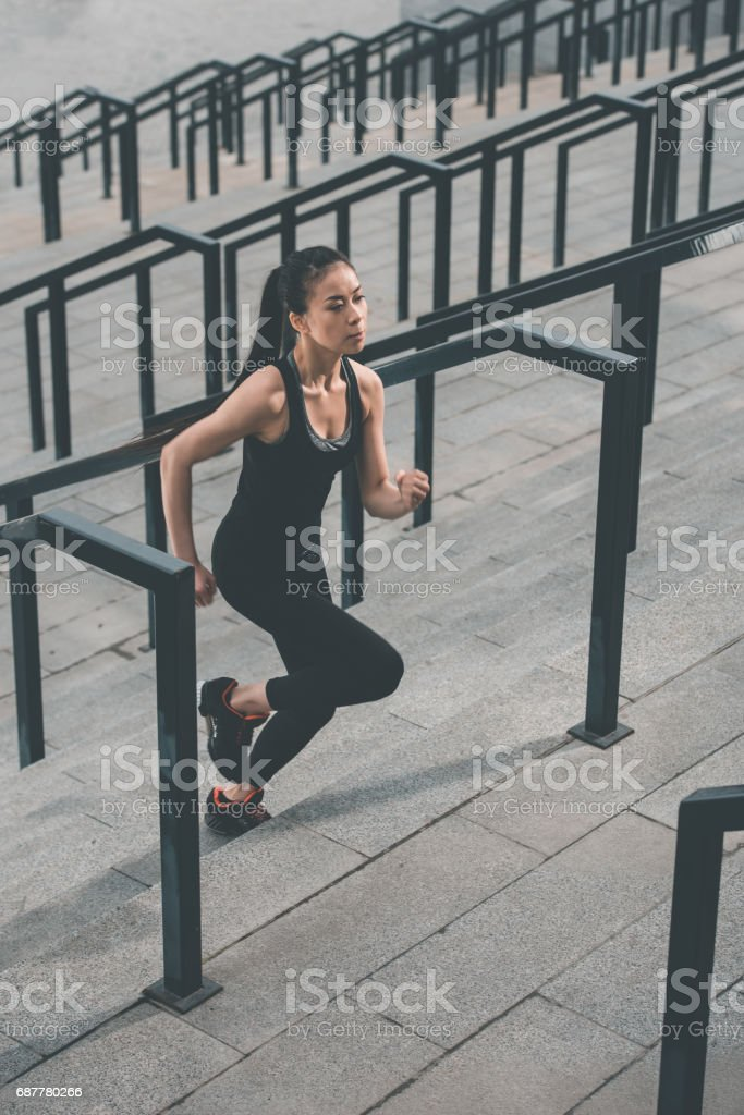 Young fitness woman in sportswear running up on stadium stairs stock photo