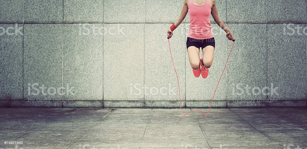 young fitness woman jumping rope outdoor stock photo