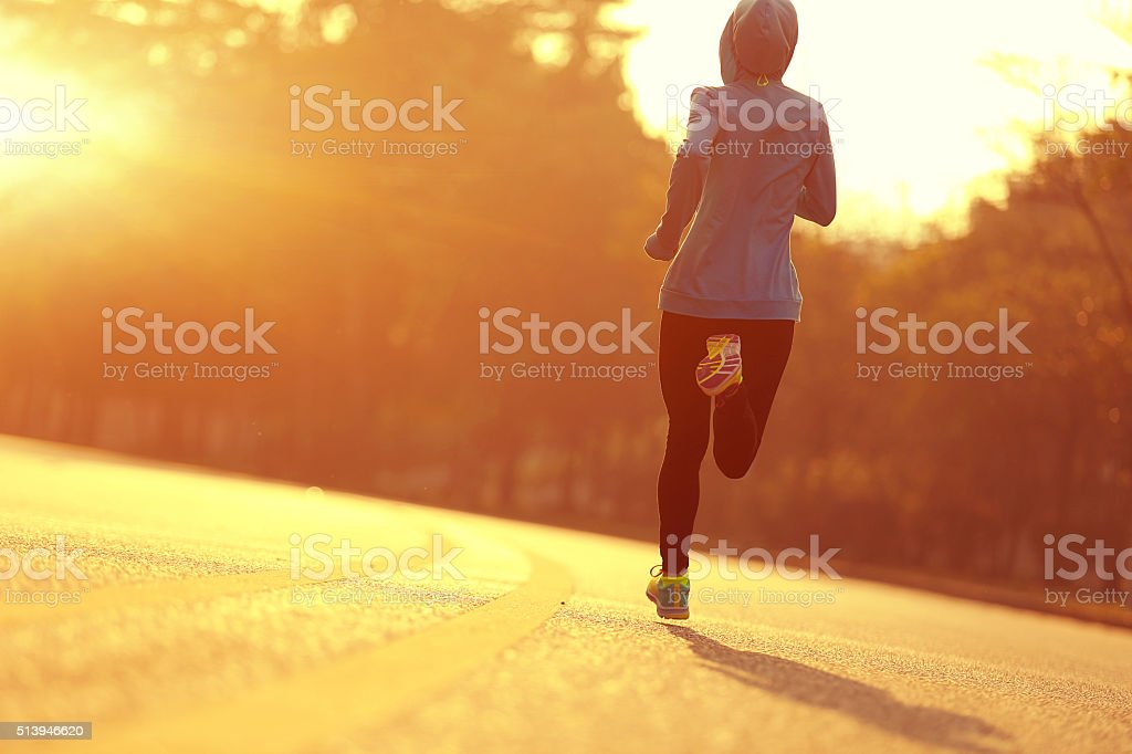 young fitness woman runner athlete running at  sunrise road stock photo