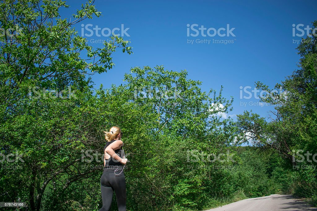 Young fitness woman runner athlete running on sunrise road stock photo