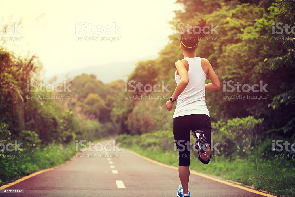 young fitness woman runner  running at forest trail stock photo