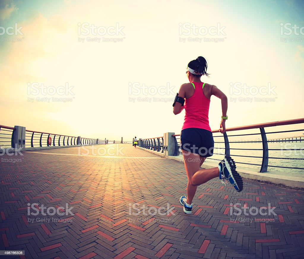 young fitness woman runner running at seaside stock photo
