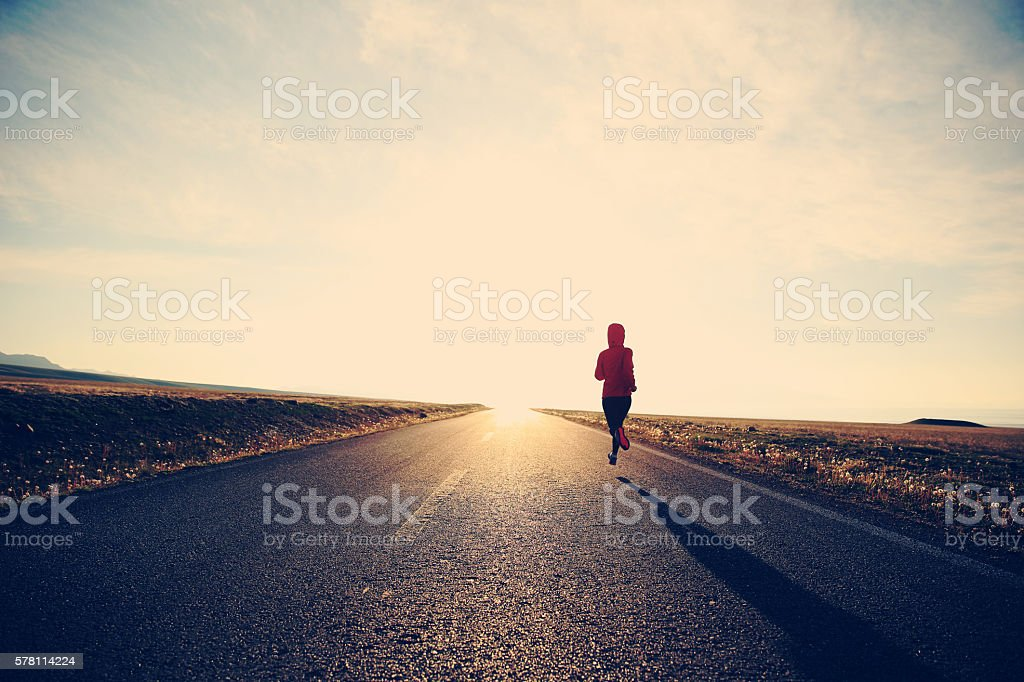 young fitness woman runner running on road stock photo