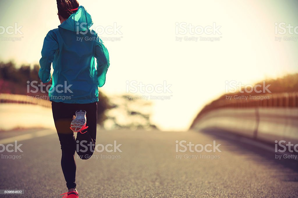 young fitness woman runner running on sunrise road royalty-free stock photo