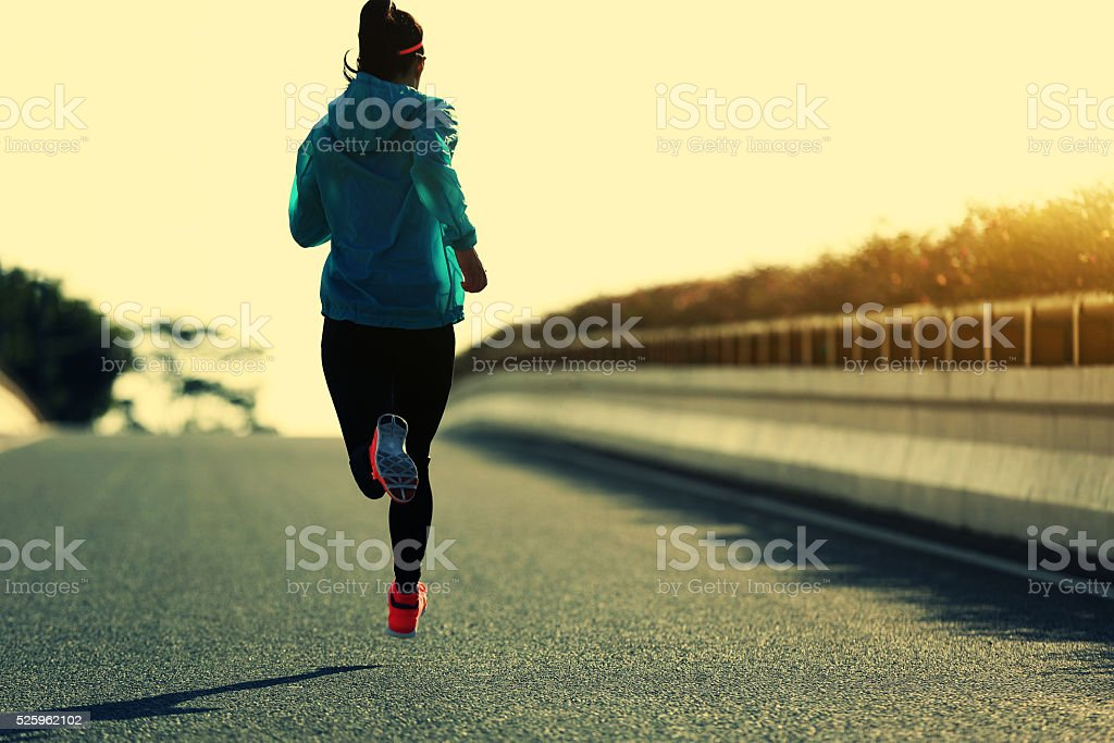 young fitness woman runner running on sunrise road stock photo