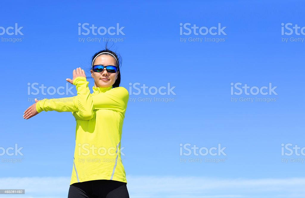 young fitness woman runner stretching arms before running on bea stock photo