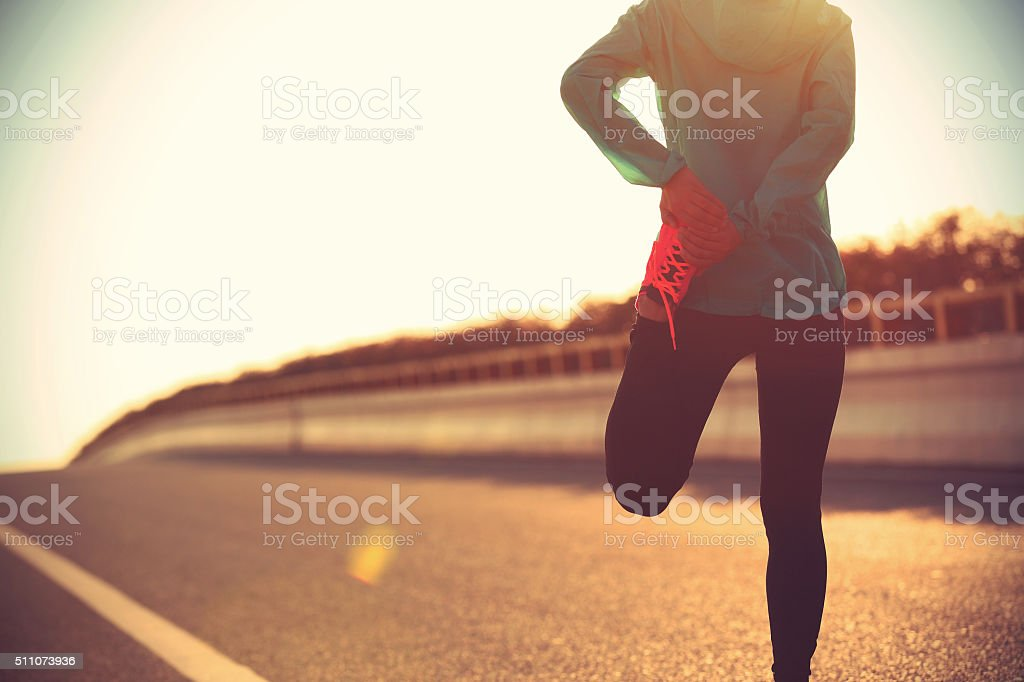 young fitness woman runner stretching legs before run stock photo