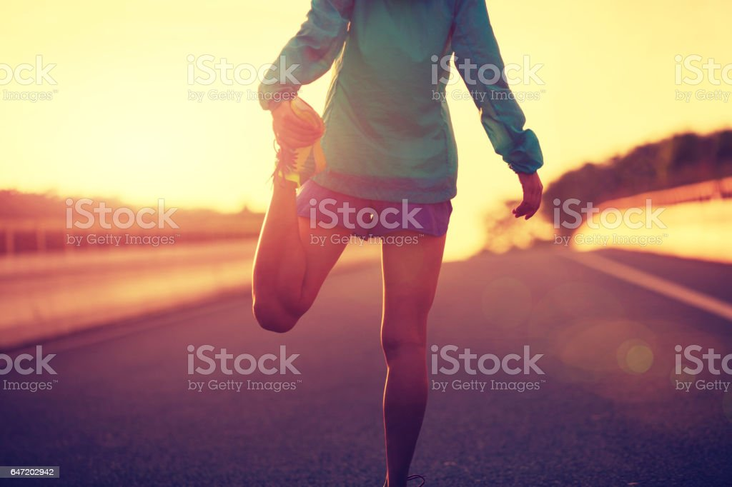 young fitness woman runner stretching legs on city road stock photo