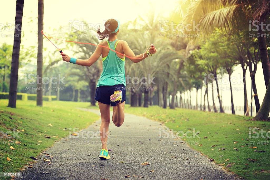 young fitness woman runner tying shoelace on road stock photo