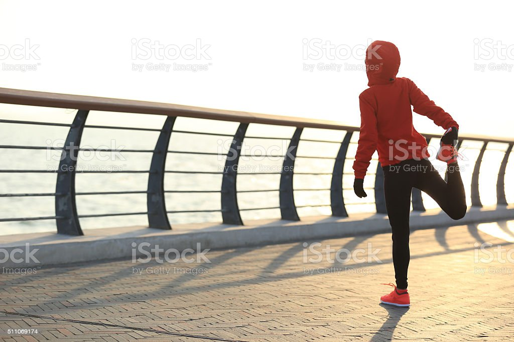 young fitness woman runner warm up at sunrise seaside stock photo