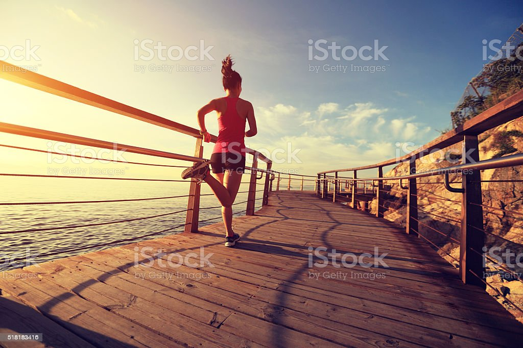 young fitness woman running on seaside wooden boardwalk royalty-free stock photo