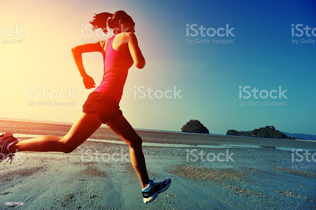 young fitness woman running on sunrise beach stock photo