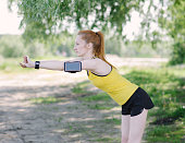 Young fitness woman stretching body before run.