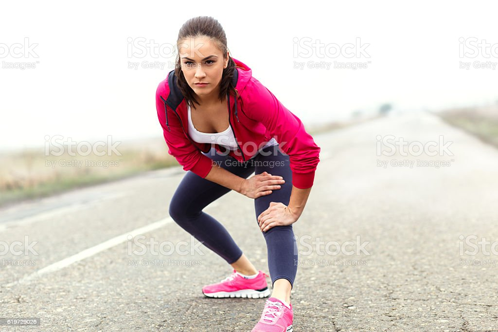 Young fitness woman stretching her muscles before running stock photo