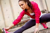 Young fitness woman stretching her muscles before running