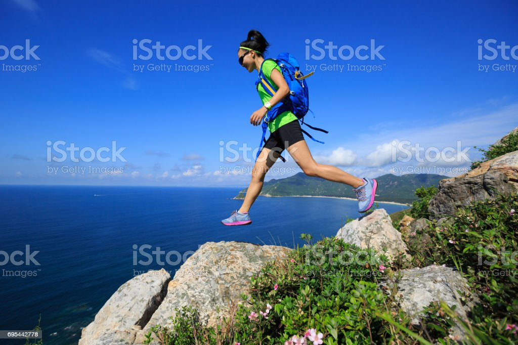 Young fitness woman trail runner running at seaside mountain rocks stock photo