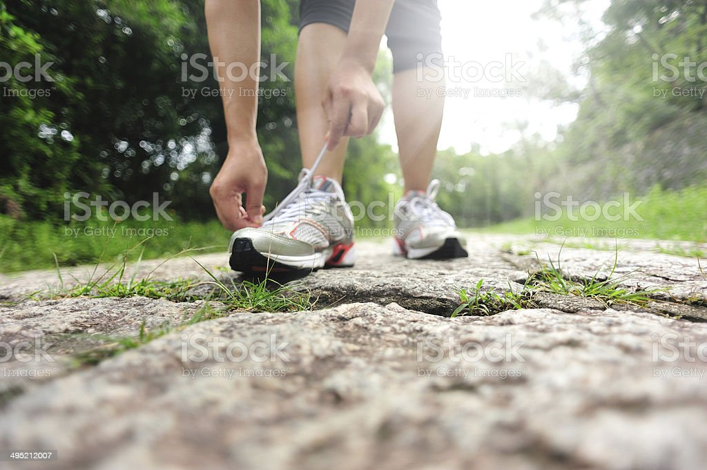 young fitness woman tying shoelaces on trail stock photo