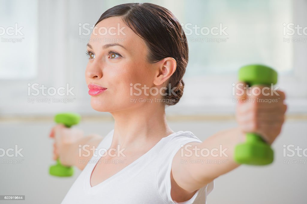 Young fitness woman working out with free weights in gym stock photo