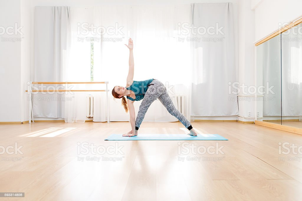 Young flexible blonde woman in utthita trikonasana triangle pose indoor stock photo