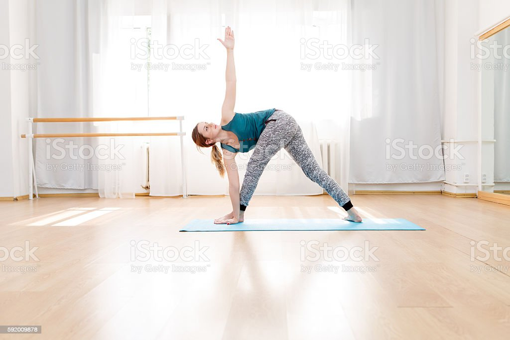 Young flexible blonde woman practicing triangle pose in yoga center stock photo
