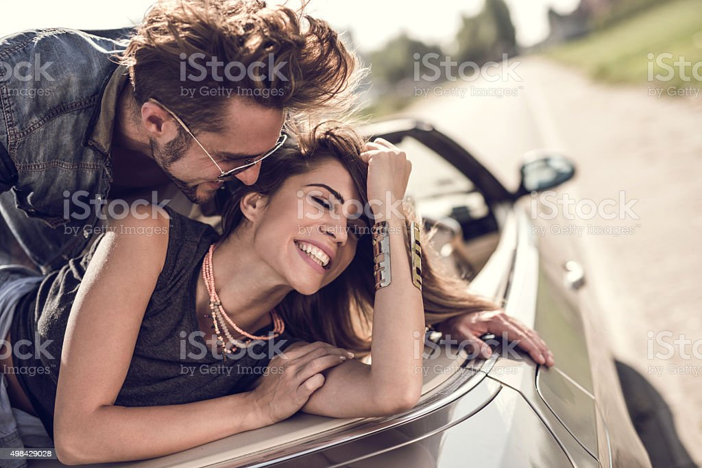 Young flirty couple enjoying in their love on a convertible. stock photo