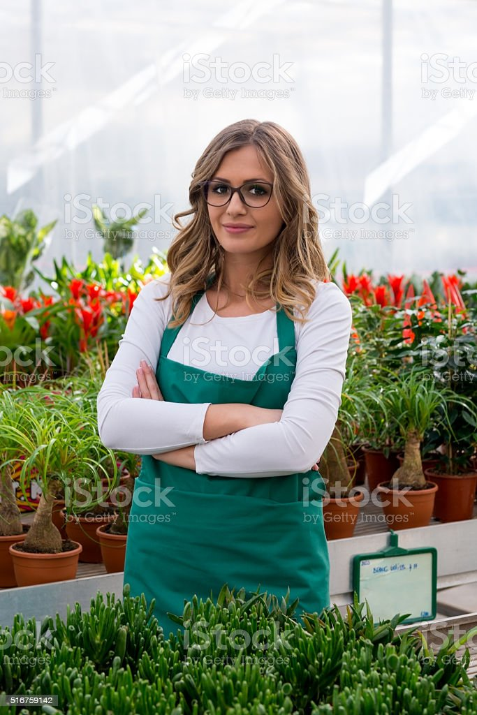 Young florist  in greenhouse stock photo