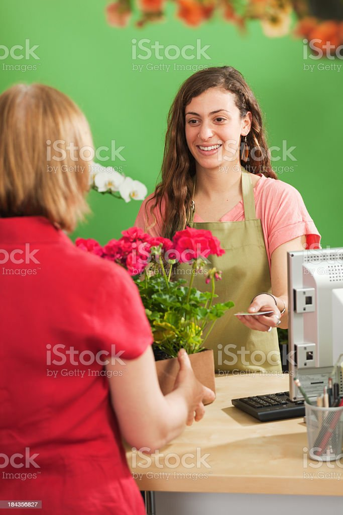 Young Flower Garden Center Sales Person Serving Retail Customer Vt royalty-free stock photo