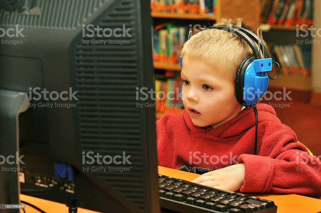 A young focused blond boy on a desktop computer stock photo