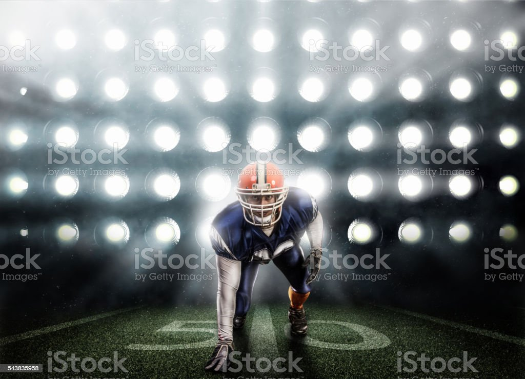 Young football player in blue uniform on background of spotlights stock photo
