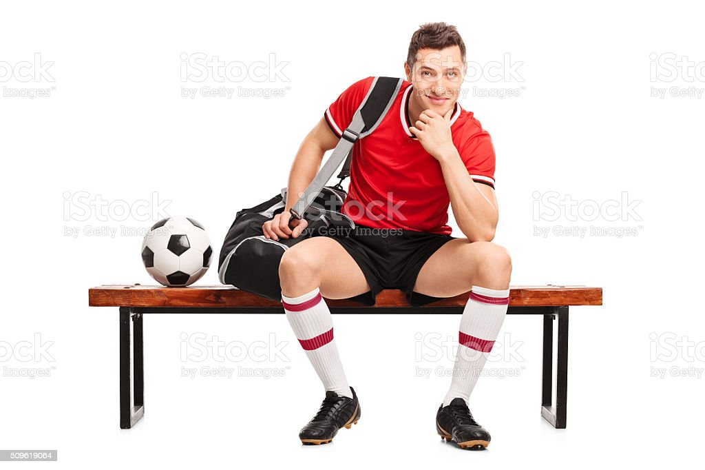 Young football player sitting on a bench stock photo