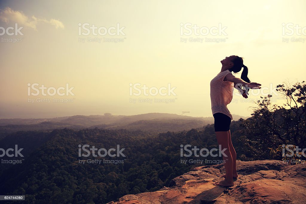 young freedom woman open arms on mountain peak stock photo