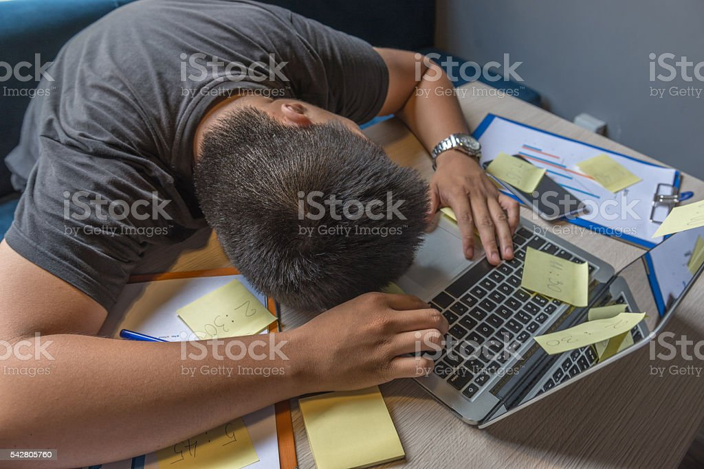 Young freelancer feel tired, frustrated and fall asleep on laptop stock photo
