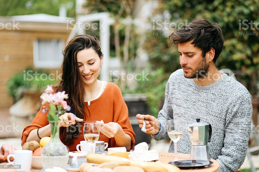 Young French couple having a brunch in the garden stock photo