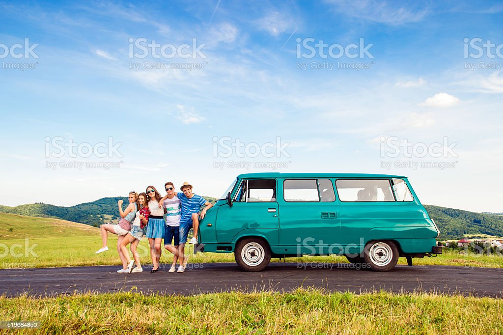 Young frieds with campervan, green nature and blue sky stock photo