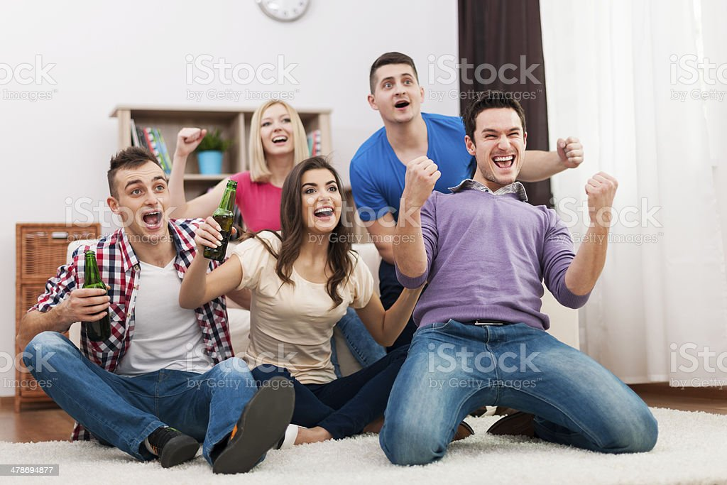 Young friend watching TV and cheering soccer stock photo
